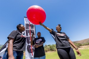 The young women release a weather balloon attached to a CricketSat they ...